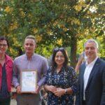 Preisträger mit Urkunde in der Hand, daneben Birgit Monteiro, Dilek Kolat und Herr Neumann