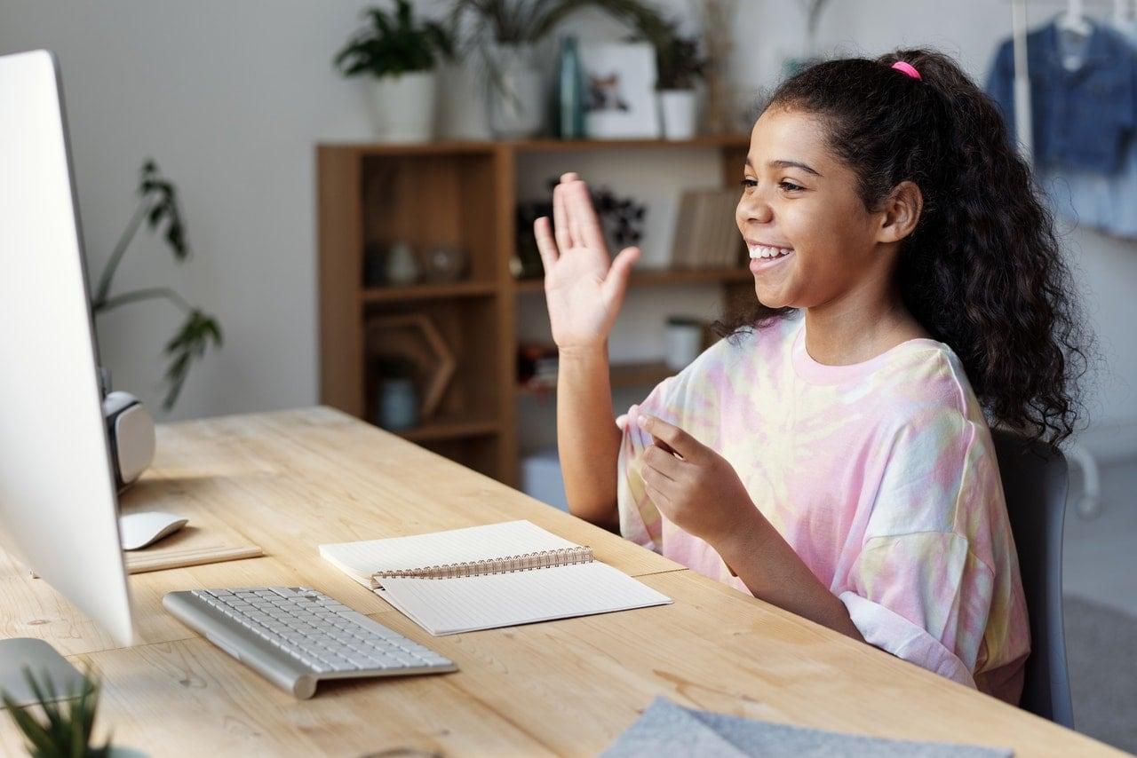 Schülerin sitzt zu Hause vor PC und winkt
